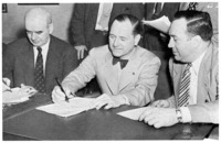 Signing the Ford-UAW contract. Left to right: Philip Murray, President of the CIO; Harry Bennett; and R. J. Thomas, President of the UAW