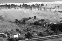 An incoming tsunami washes over a stretch of houses and buildings. The sea is visible in the top left, with the waves sweeping towards the bottom right. A thin line of trees is visible, as the waves sweep past into the neighborhood. Ruins of houses can be seen, as well as a few remaining houses and buildings.