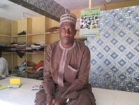 Textile trader-broker in Kano market shop.