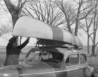 A photograph of a canoe strapped to the top of a car.
