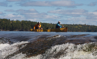 A color photograph of two canoeists paddling Wenonah Kevlar canoes.