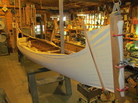 Canvas being stretched over a 1905 Morris Veazie model canoe. Note the tacks at the gunwale that hold the canvas to the boat.