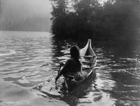 A black-and-white of a figure paddling a dugout canoe.