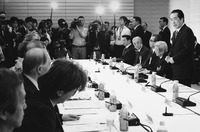 A long table with identical sets of microphones, drink bottles, and paperwork. Formally dressed people sit on both sides, with one man on the right side standing and talking.  Photographers and onlookers line the far side of the table.
