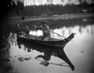 A black-and-white photograph of a family of three in a dugout canoe: two adults and one small child. One of the adults is throwing a double pronged sealing spear into the water.