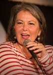 Photo of Roseanne Barr holding a microphone.
