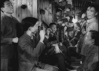 Passengers in a train car gather together and socialize.