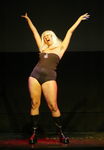 Figure 16. Aya de León as Lady Triple X in Thieves in the Temple (2002). Lady Triple X is a female emcee wearing a blonde wig, black spandex panty shorts, a black tube top, and black heels.