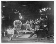 In this photograph, the officer-in-transit (Kelberer) sprawls on the stage (left) and Khlestakov (Garin) lies collapsed in a chair (right), both in a drunken stupor, while the Major's wife (Raikh) guides the town officials out on tiptoe.