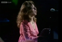 Figure 13. Carole King, wearing a pink dress, sits at the piano and sings with her eyes closed and an expression of deep immersion in the music on her face.