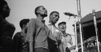 The Freedom Singers (from left): Rutha Mae Harris, Bernice Johnson (partially hidden), Cordell Reagon and Charles Neblett are joined by Pete Seeger (far right) in performance at the 1963 Newport Jazz Festival. Photograph copyright Daniel Gomez-Ibanez, 1963.