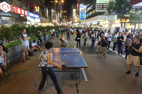 This photograph shows two individuals playing table tennis in the middle of a street at night. The street is crowded with pedestrians and several people are watching the game.