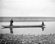 A black-and-white photograph of two people poling a dugout canoe on the Columbia River in 1900.