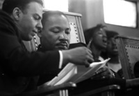 Dr. Martin Luther King Jr. and Andrew Young compare notes while a choir sings during a church meeting in Greenville, Alabama in December 1965.