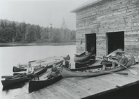 Myron Nickerson, a former employee of J. Henry Rushton appears on the far right in this 1894 photograph. Nickerson's livery on the Grasse River in Canton, New York, offered rentals of Adirondack guideboats, Rushton-style pleasure rowboats, small skiffs, and canoes. Nickerson holds a double-bladed canoe paddle in a boat that has also been fitted with non-feathering guideboat-style oars.