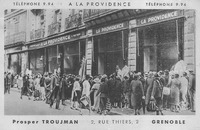 A postcard showing a photograph of the storefront for A La Providence with a crowd in front. Along the edges of the postcard are the telephone number, store name, owner, and address.