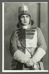 Photograph of Alisa Koonen in the armor of Joan of Arc, her heavily gloved hands clasped in front of her, her eyes to one side.
