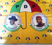 "Textile depicting photographs of  ""H.E. Chief James Onanenefe Ibori"" and of ""H. E. Senator Ifeanyi Athur Okowa"" beneath a large umbrella reading ""PDP."""