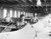 A black-and-white photograph of employees at the Old Town Canoe Company constructing canoes.