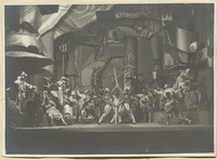 Photograph of Giglio (Ferdinandov) and his Doppelgänger (Vigilev), center, wearing half masks with long, curved noses and dueling with swords while others in black half masks look on. Upstage, standing on one of the set's several raised sections, stands a figure in black, Celionati (Shchirsky), seemingly conducting the duel as it progresses.
