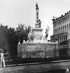Figure 1 depicts a monument located in a fenced grassy area adjacent to the United States Capitol building, which is visible on the side of the image. The photograph is historic and shows the location around the year 1857. At the center, the Naval or Tripoli monument dominates the scene. The monument contains, from the top, an eagle and shield on a rostral column. Viewed from the side, the photograph shows three of the ship's rams on the column; another three are not visible from this angle. Around the column and on a base below it a viewer encounters numerous relief sculptures, examples of freestanding figural statuary, and inscriptions. Important for this study are the small sculptures lining the upper edges of the column's base that depict Orientalizing and caricaturesque faces meant to represent the peoples of the Maghreb.