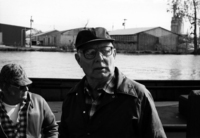 A portrait of a Lake Erie Fisherman wearing glasses and a hat, looking slightly left to the camera.