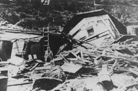 A black and white photograph of a person standing amidst the ruins of a building. Behind them, to their left, the remains of an upper floor of the building remains somewhat intact, atop the rubble.