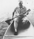 A black-and-white portrait of Leroy Grumman paddling an aluminum canoe.