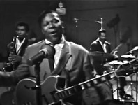 Figure 7. Blues musician B. B. King, dressed in a suit and fronting a full band, sings at a microphone with his eyes closed and without playing his guitar.