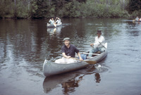 A color photograph of Gaylord Nelson and others paddling aluminum canoes.