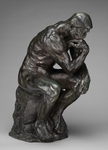 Photo of a sculpture titled The Thinker by Rodin. This is a bronze sculpture of a naked man in a sitting position with his left arm draped over his knee and his right elbow on his knee. His hand is bent under his chin as if he is thinking