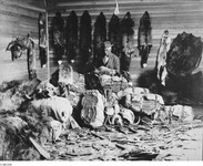 A black-and-white photograph of a figure sitting in a room full of furs.