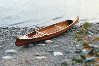 A color photograph of the canoe Turtle Dove V, resting on a rocky beach.