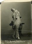 Photograph of Samuil Vermel as Pierrot, his costume white with black pompoms, standing, head back, with a hand on a chair.