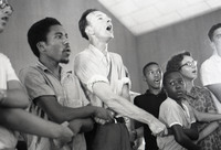 "Free Southern Theater guitarist Roger Johnson crosses his arms and joins hands with legendary folk singer and activist Pete Seeger to sing ""We Shall Overcome"" at Mt. Zion Baptist Church, August 4, 1964, during the Freedom Summer in Hattiesburg, Mississippi."