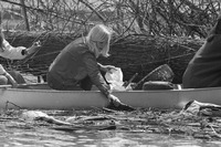 A black-and-white photograph of a Girl Scout in a canoe, picking litter out of a waterway.