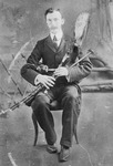Portrait of a man sitting in a chair holding uilleann pipes (Irish bagpipes).