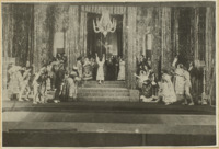 Pierrette (Koonen), dressed in wedding white, stands on the ballroom steps (center), her arms raised in alarm as she sees Pierrot's ghost, a diaphanous puppet manipulated by a visible actor, upstage. Curious wedding guests watch her from both sides of the stage.
