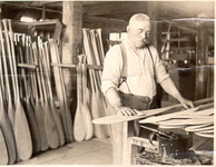 A black-and-white photograph of a figure making paddles.