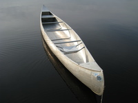 A color photograph of an aluminum Grumman canoe on the water.