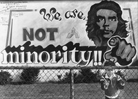 "A black and white photograph of a city mural with a male Chicanx activist pointing at ""you""; in front of it, a child behind a chainlink fence."