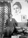 Photograph of Meyerhold standing in his study, leaning against his desk with a portrait of Zinaida Raikh (as Anna Andreevna in Inspector General) behind him and a wayang golek puppet profile just visible on the far right.
