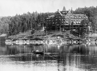 A black-and-white photograph of the Hotel Ampersand, looming over Lower Saranac Lake in the Adirondacks ca. 1890.