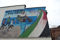 A mural painted on a building depicts a Palestinian man carrying a bleeding boy on a Gaza beach. At right is a blood-stained Palestinian flag.